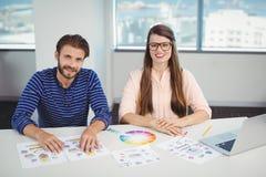 坐在书桌的微笑的图表设计师画象  免版税库存图片