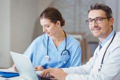 坐在书桌的微笑的男性医生画象  免版税图库摄影