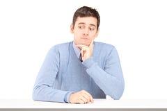 坐在书桌的担心的年轻人 免版税库存照片