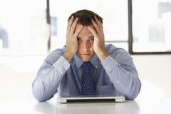 坐在书桌的沮丧的商人在办公室使用膝上型计算机 免版税库存照片