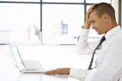 坐在书桌的沮丧的商人在办公室使用膝上型计算机 库存照片