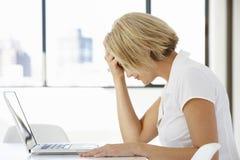 坐在书桌的沮丧的女实业家在办公室使用膝上型计算机 免版税库存照片