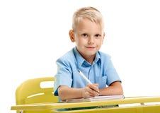 坐在书桌的男小学生 库存图片