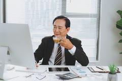 坐在书桌的确信的高级亚洲商业领袖 库存图片
