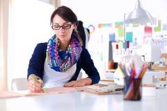 坐在书桌的美丽的时装设计师在演播室 免版税库存图片