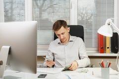 坐在书桌的衬衣的严肃和大字书写的商人,运转在有现代显示器的计算机 经理或工作者 免版税库存照片