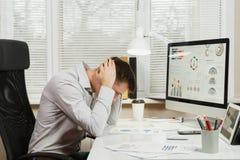 坐在书桌的衬衣的严肃和大字书写的商人,运转在有现代显示器的计算机 经理或工作者 库存照片