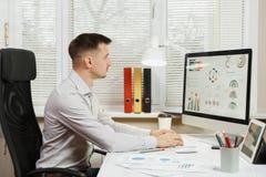 坐在书桌的衬衣的严肃和大字书写的商人,运转在有现代显示器的计算机 经理或工作者 免版税图库摄影