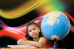 坐在书桌的逗人喜爱的学生的综合图象 免版税库存照片