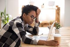 坐在书桌的非洲妇女在办公室和睡觉 免版税库存图片