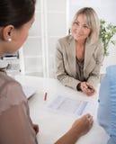 坐在书桌的顾问、经纪和顾客在办公室 免版税库存图片