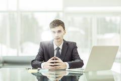 坐在书桌的年轻令人想往的商人在一台开放膝上型计算机前 库存照片
