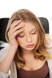 坐在书桌的年轻担心的妇女 免版税库存照片