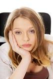 坐在书桌的年轻担心的妇女 库存照片
