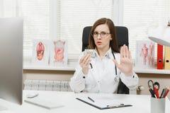 坐在书桌藏品捆绑的女性医生美元兑现金钱,对贿款说不,显示与棕榈的中止姿态 免版税库存图片