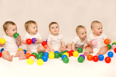 坐在五颜六色的球中的五个逗人喜爱的婴孩 新生儿党  免版税库存照片