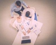 坐在他们的有膝上型计算机的书桌的两个商人 顶视图 免版税库存图片