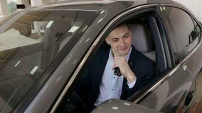 坐在他有钥匙的新的汽车后轮子的愉快的商人  股票视频