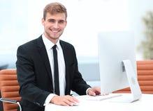 坐在他的书桌的确信的商人 库存照片