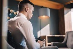 坐在他的办公室的年轻人,但是兴旺的商人使用电话 库存图片
