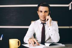 坐在他的工作地点的聪明的便衣的可爱的商人在拿着一个巧妙的电话的办公室 库存图片