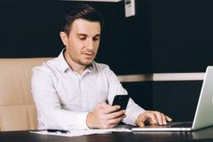 坐在他的工作地点的聪明的便衣的可爱的商人在拿着一个巧妙的电话的办公室 免版税库存照片