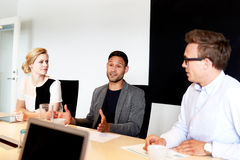 坐在会议室的小组年轻董事 免版税库存照片