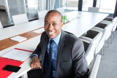 坐在会议桌上的微笑的年轻商人画象  库存图片