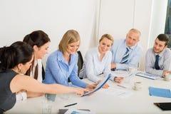 坐在会议桌附近的企业队 免版税库存图片