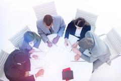 坐在会议桌附近的大角度一个不同的集团 免版税库存图片