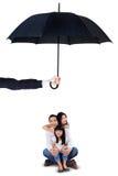 坐在伞下的快乐的家庭在演播室 库存图片
