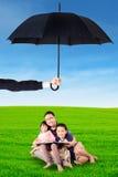 坐在伞下的爸爸孩子 图库摄影