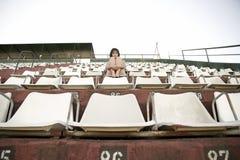 坐在体育场内的减速火箭的女孩 免版税库存图片