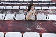 坐在体育场内的减速火箭的女孩 库存图片