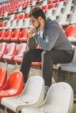 坐在体育场cheirs的运动员 库存图片