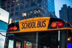 坐在停车处的校车儿童教育运输在纽约街道的晚上 免版税库存照片