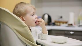 坐在儿童位子的小男孩在厨房和从板材是非常鲜美食物 微笑和戏剧 股票录像