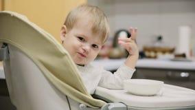 坐在儿童位子的小男孩在厨房和从板材是非常鲜美食物 微笑和戏剧 股票视频