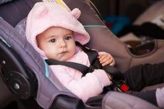 坐在儿童位子的逗人喜爱的女婴 免版税库存图片