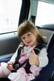 坐在儿童安全位子的汽车的小逗人喜爱的女孩 免版税库存照片