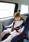 坐在儿童安全位子的汽车的小逗人喜爱的女孩 图库摄影