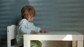 坐在儿童的桌和轮上的女婴她的在慢动作的头 股票录像