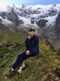 坐在光彩的Humantay湖前面的一个年轻游人,高在安第斯山脉,沿Salkantay足迹在秘鲁 库存图片