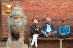 坐在入口的尼泊尔人对Patan博物馆在尼泊尔 免版税库存图片
