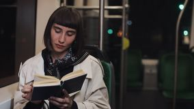坐在公共交通工具,steadicam的年轻女人或乘客看书射击了 t 城市光背景 股票视频