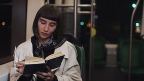 坐在公共交通工具,steadicam的年轻女人或乘客看书射击了 t 城市光背景 股票录像