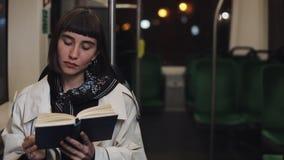 坐在公共交通工具,steadicam的年轻女人或乘客看书射击了 t 城市光背景 影视素材