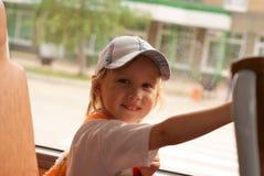 坐在公共汽车上的微笑的小女孩 免版税库存图片