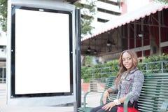 坐在公共汽车站长凳的妇女 免版税库存照片