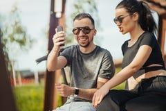 坐在公园和做selfie的年轻人和妇女夫妇  免版税库存照片